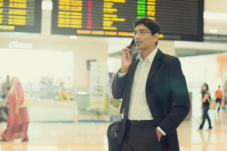 business traveller: indian business male with a phone at the airport
