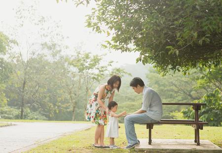 familias jovenes: Familia asiática feliz disfrutando de su tiempo en el parque