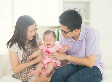 padre asiático con el bebé llora