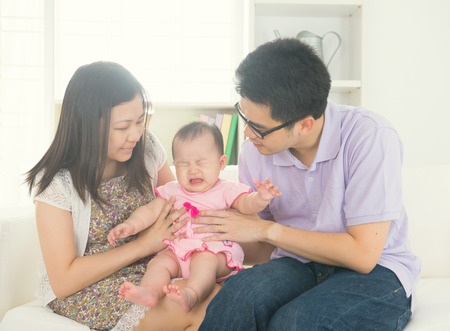 bebe enfermo: padre asiático con el bebé llora