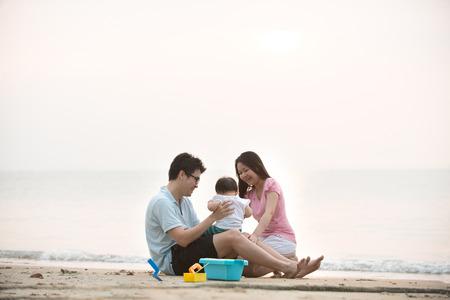 familias jovenes: Familia asi�tica feliz jugar en la playa