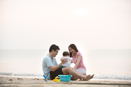 Glückliche asiatische Familie spielen am Strand
