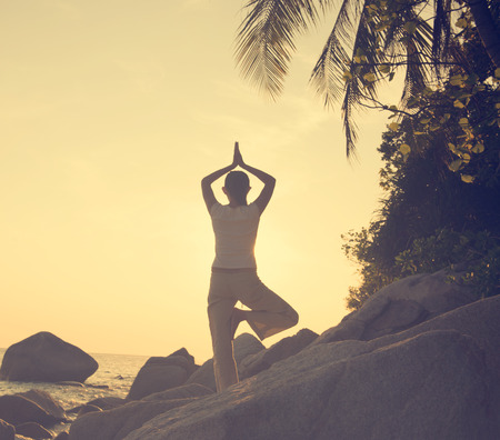 composure: Woman practicing yoga on the beach at sunset, vintage tone
