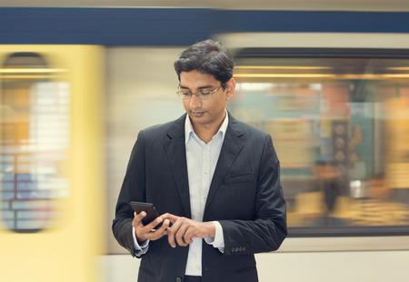 駅で電車を待っている間にスマート フォンを使用してアジアのインドのビジネスマンのテキスト メッセージ