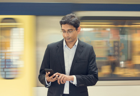 railroad transportation: Asian Indian businessman texting using smartphone while waiting train at railway station