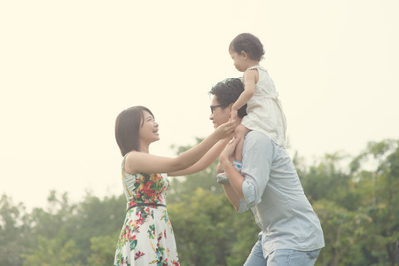 asian family playing and enjoying quality time outdoor , vintage tone Imagens