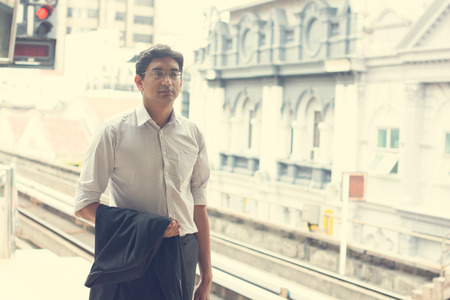 Candid Asian Indian businessman waiting at public train station. photo