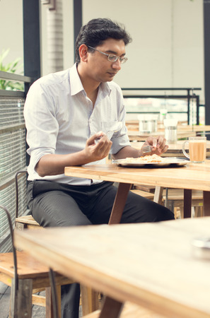lunch hour: Asian Indian business man reading newspaper while drinking a cup hot milk tea during lunch hour at cafeteria.