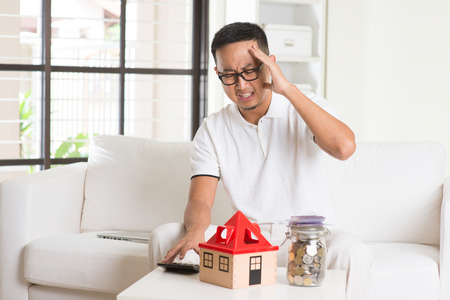 financial burden: asian casual male and house loan Stock Photo