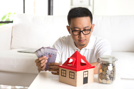 home expenses: asian casual male and house loan Stock Photo