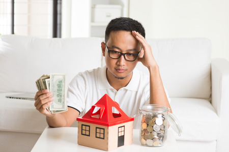 mortgages: asian casual male and house loan Stock Photo