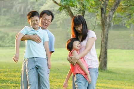 asian family outdoor: Asian Family Enjoying Walk In Summer Countryside