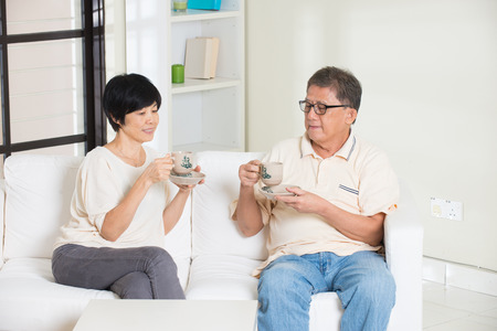 asian senior couple having drinks while relaxing photo