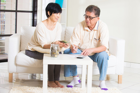asian senior couple calculating finance at their home