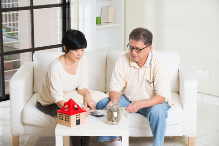 refinance: asian senior couple calculating home mortgage