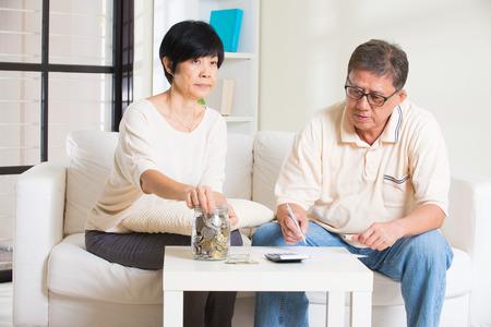 debt goals: asian senior couple calculating finance at their home