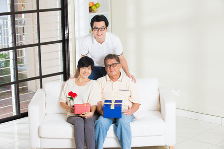 three gift boxes: asian man giving present to father and mother