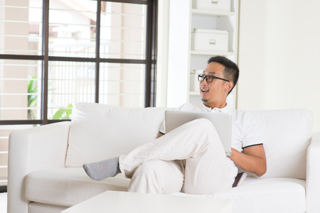 southeast asian: Southeast Asian male using internet at home,
