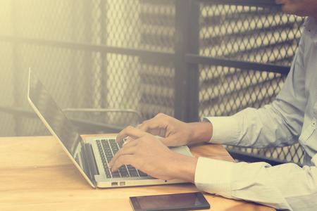 usando computadora: Hombre de negocios indio asiático que usa smartphone y el ordenador portátil en la cafetería al aire libre.