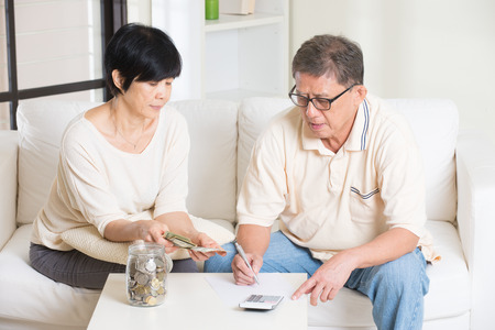 savings goals: asian senior couple calculating finance at their home