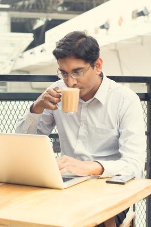 tomando leche: Empresario indio de Asia usando el ordenador portátil mientras bebe una taza de té de leche caliente. Foto de archivo