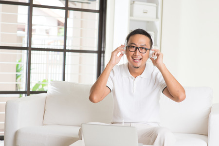 happy smiling:   Smiling Southeast Asian college student relaxing and listening to music at home  Stock Photo