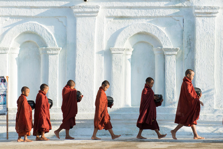 alms: INLE LAKE, MYANMAR - JULY 10 : Buddhist novices walk to collect alms and offerings on JULY 10,2015 in Mandalay, Myanmar. This procession is held every day. Editorial
