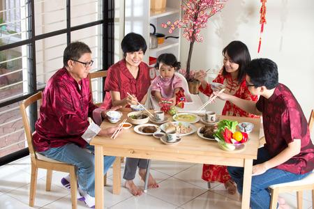 familia cenando: Nuevo año la cena reencuentro chino, que forma parte de la cultura china para recopilar durante víspera Foto de archivo