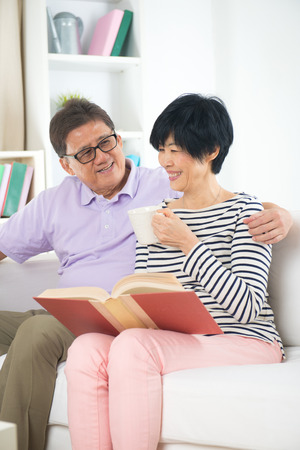 old asian: senior asian couple reading a book together at home. Stock Photo