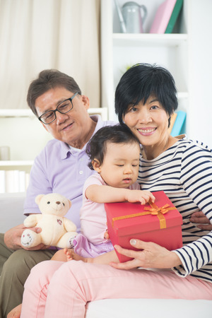 asian grand parents with grand daugther celebrating christmas