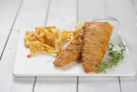 british food: Fish and chips. Fried fish fillet with french fries wrapped by paper cone, on wooden background. Fresh cooked with hot smoke.