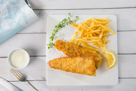 plato de pescado: Pescado y papas fritas. Filete de pescado frito con papas fritas envueltas por cono de papel, sobre fondo de madera. Foto de archivo