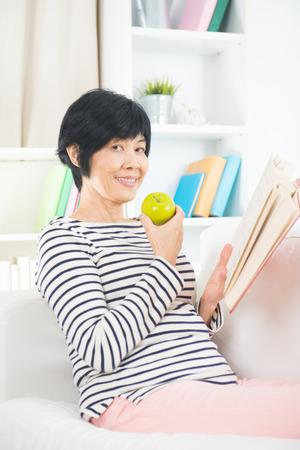 vegetarian food: asian senior female eating apple