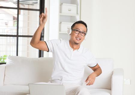eyesclosed: casual asian man enjoying music in livingroom Stock Photo