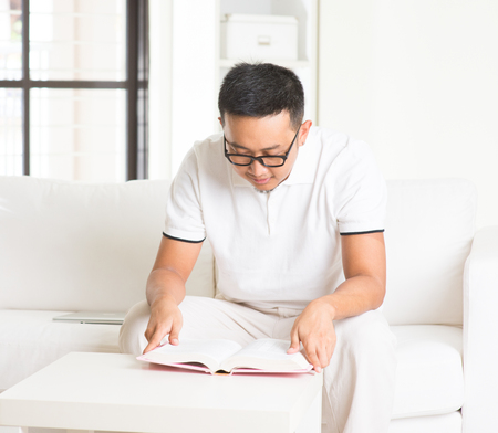 assignment: casual asian man reading in livingroom