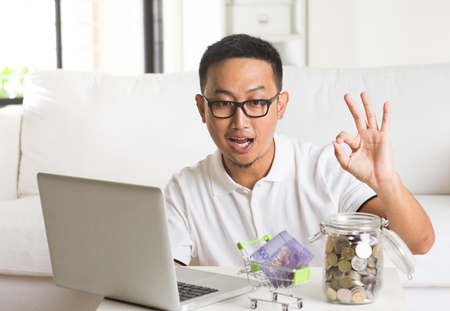 asian guy using internet computer and counting coins at home. Asian man relaxed and sitting on sofa indoor. Archivio Fotografico
