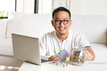 gift spending: asian guy using internet computer and counting coins at home. Asian man relaxed and sitting on sofa indoor. Stock Photo