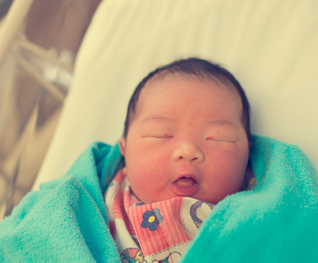 bed skirt: asian newborn on bed Stock Photo
