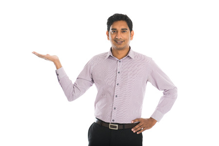 point of view: portrait of young businessman pointing at invisible product over white background.
