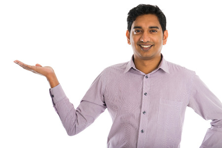 indian business man: portrait of young businessman pointing at invisible product over white background.
