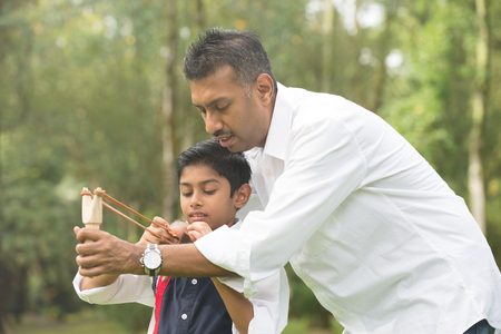 father and son: indian father and son playing slingshot at the park Stock Photo
