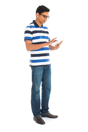 Happy young man using digital tablet against white background.