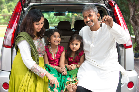 buying a car: Happy Asian Indian family sitting in car talking and smiling happily