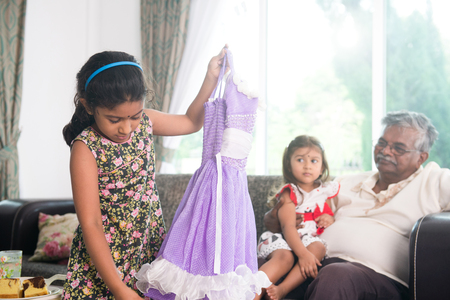 daugther: indian grand daugther trying out diawli dress for the grandfather Stock Photo