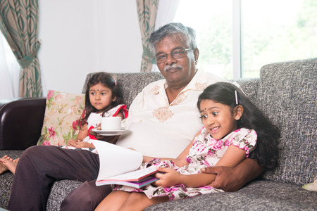 family at home: indian grandfather learning with his granddaughters Stock Photo