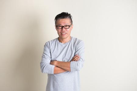 vecchiaia: maschio asiatico anziano casuale, braccio attraversato Archivio Fotografico