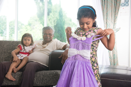 indian grand daugther trying out diawli dress for the grandfather Imagens