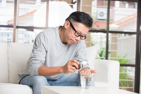 senior men: asian senior male taking pills in despair Stock Photo