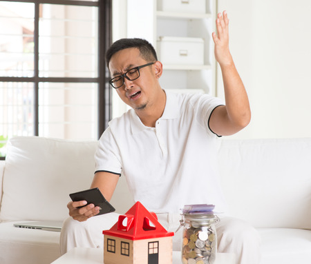 trouble: asian man stress on high property price and debts