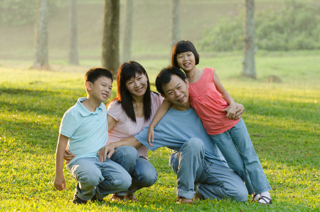 eight years old: Family lying outdoors being playful and smiling, Outddor portrait